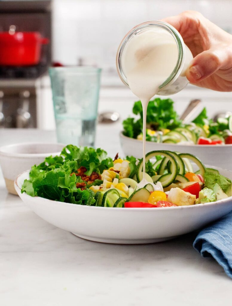 romaine lettuce, coconut bacon, grilled corn, cherry tomatoes, and cashew dressing in white bowl