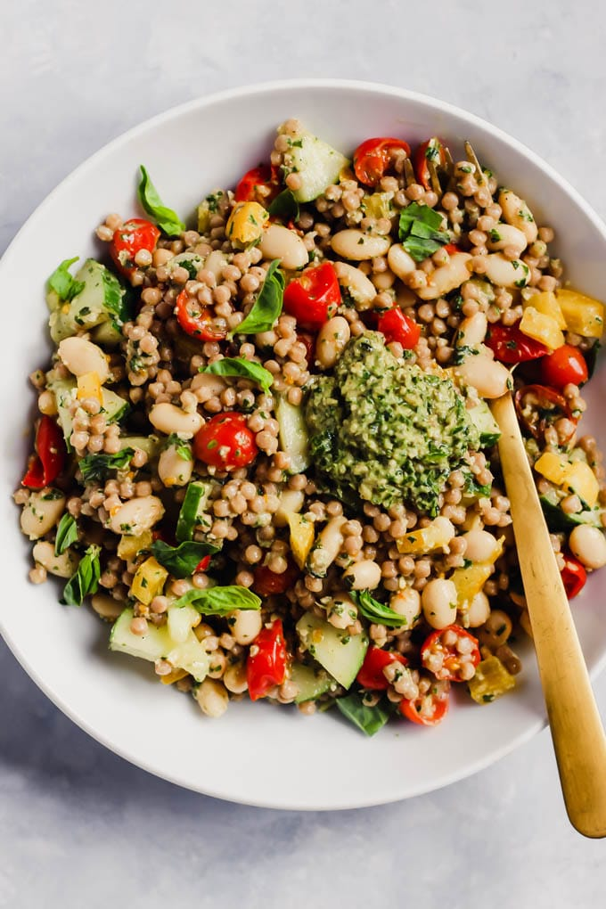 couscous with tomatoes, bell peppers, white beans, and pesto in a white bowl