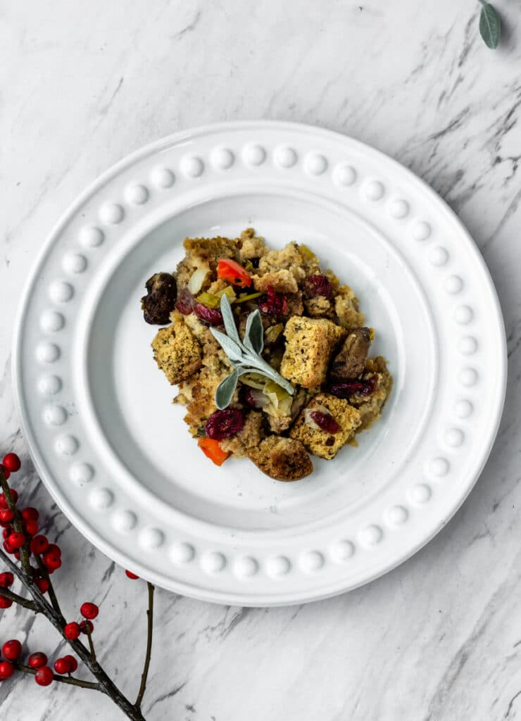 a slice of cornbread stuffing on a white plate with sage on top