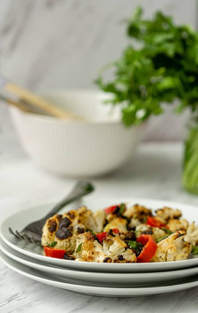 roasted cauliflower with cilantro and fresno peppers on white plate with fork