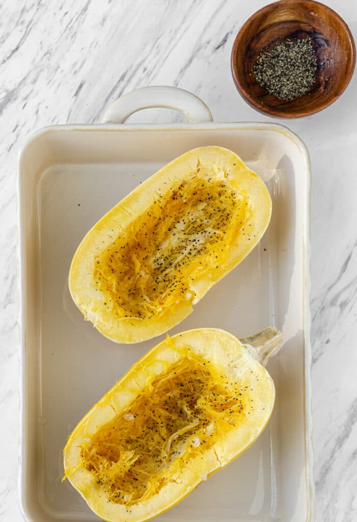 cut in half squash with black pepper and salt in pan