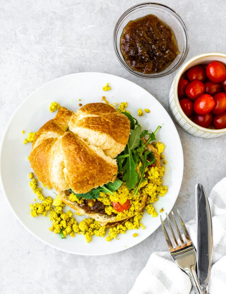 tofu scramble recipe with tomatoes, fig preserve, spinach, and vegan croissant