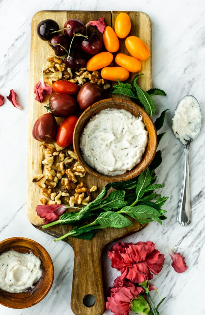 a platter of vegetables and nuts with vegan feta cheese
