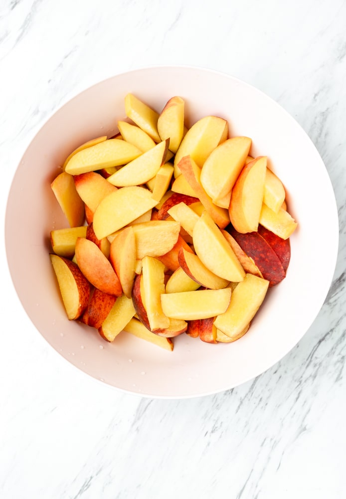 sliced peaches in a pink bowl