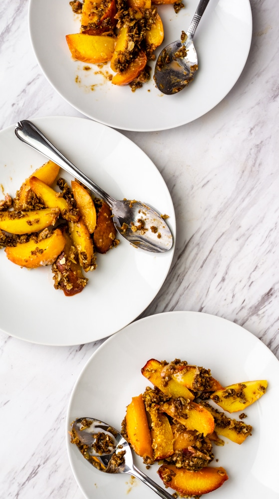 peach crisp on white plates with spoons