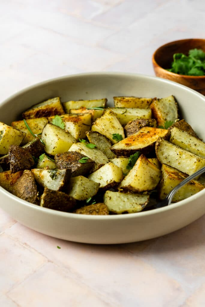 garlic roasted potatoes in tan bowl with parsley in wooden bowl