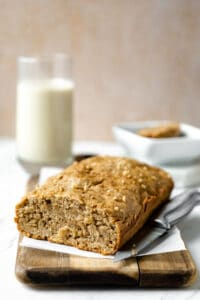 vegan banana bread on wooden cutting board with oat milk and sliced bread