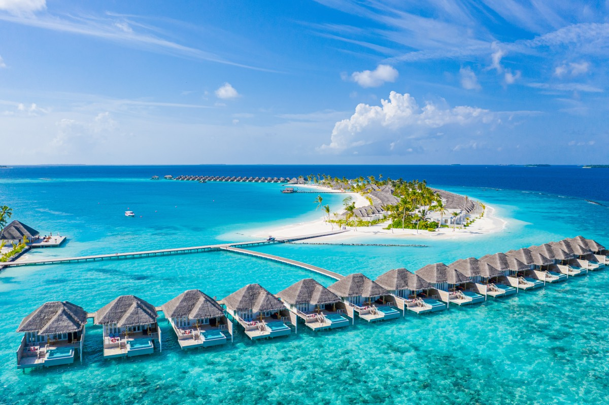 Perfect aerial landscape, luxury tropical resort or hotel with water villas and beautiful beach scenery. Amazing bird eyes view in Maldives, landscape seascape aerial view over a Maldives