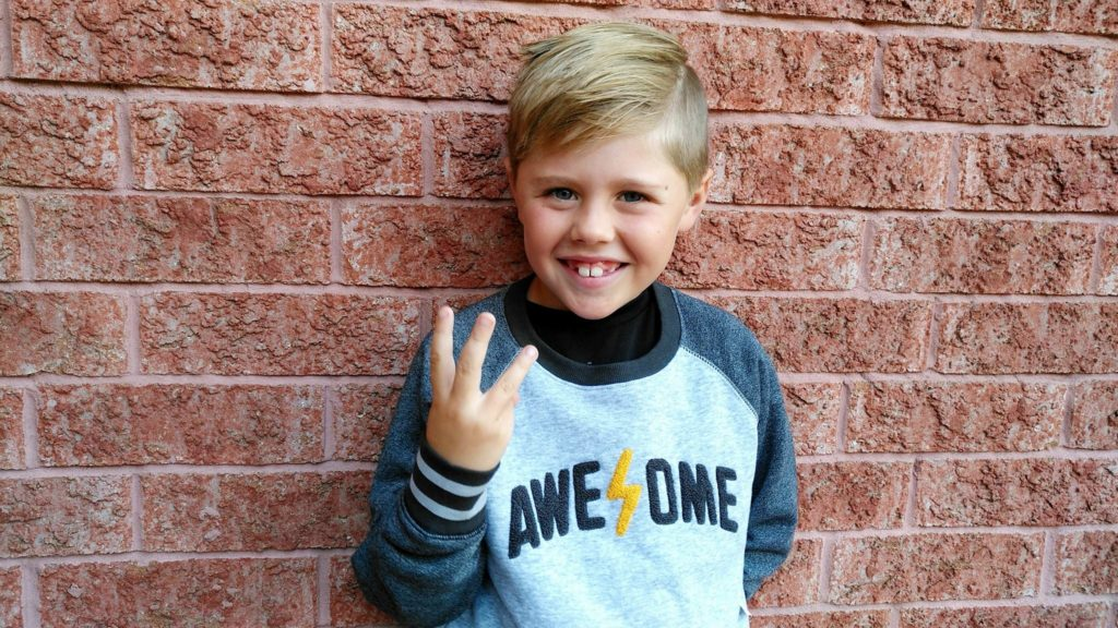 Cooper holding up three fingers to show he's going to grade 3