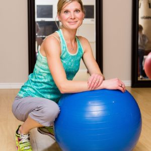 Christina, TKL's Trainer, based in Barrie, leaning on an exercise ball