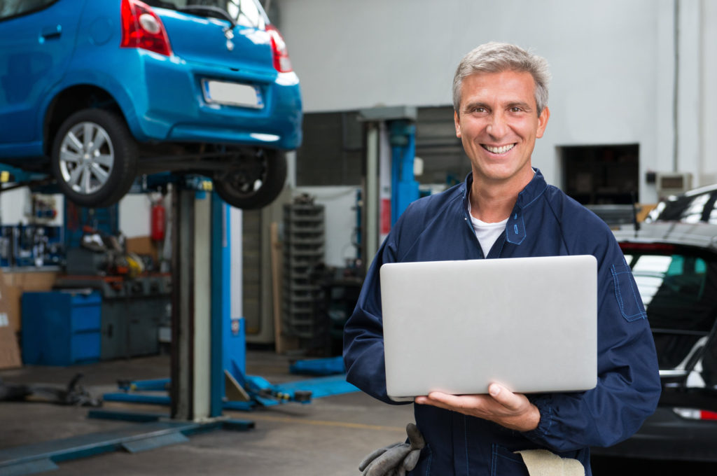 Portrait Of Happy Mature Mechanic At Repair Service Station With Laptop