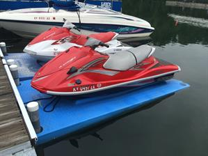 Side profile of a white-and-red and pure red water scooters parked at a marina dock