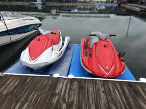 A white-and-red and pure red water scooters parked at a marina dock