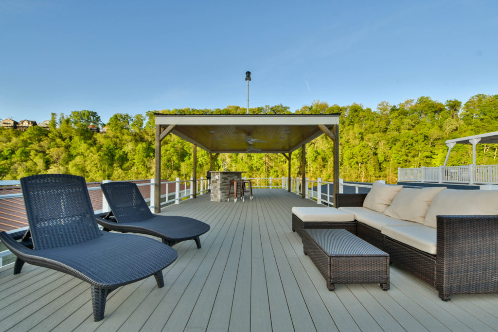 Roof deck of a houseboat that has a partial cover and two woven lounges and a woven sofa