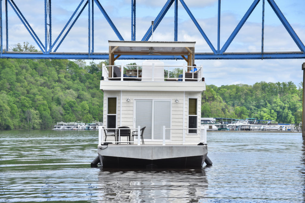 Open deck on the bow of a cream houseboat in the middle of a body of water