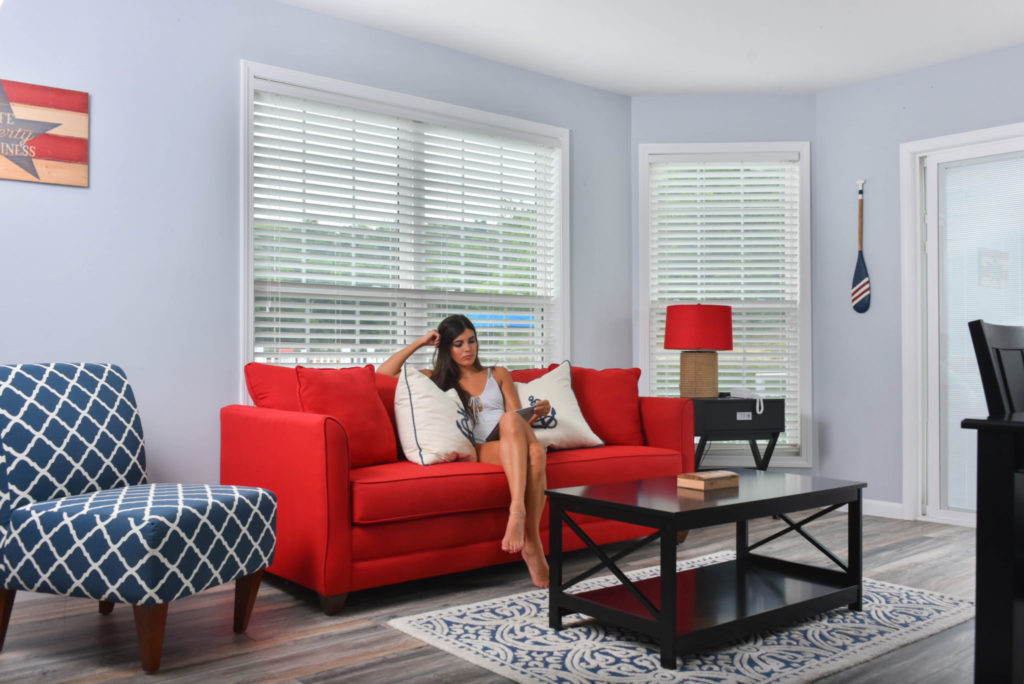 Woman reading a book in a pastel grey living room with a red couch, blue loveseat, and black tables