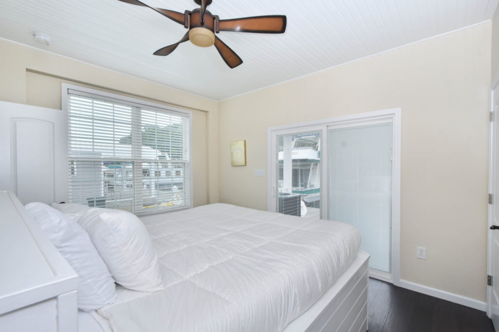 Cream-colored bedroom with a white bed and a brown ceiling fan