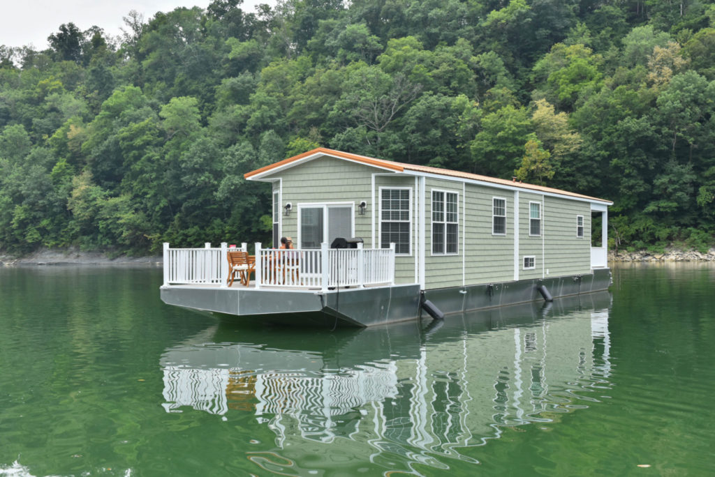 Open deck on the bow of a green houseboat in the middle of a body of water