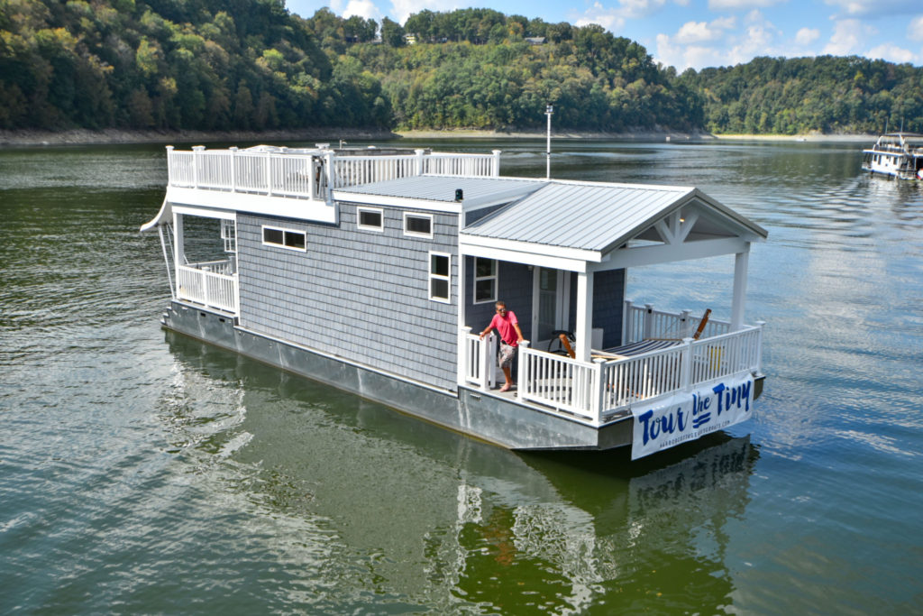 Small blue houseboat in the middle of a body of water
