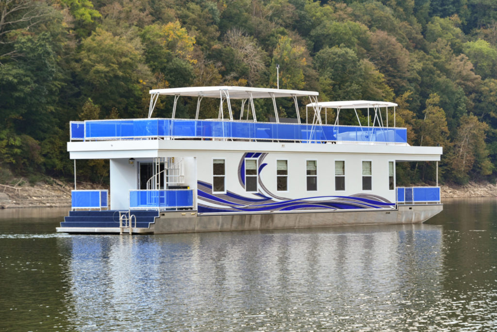 White houseboat with blue and grey accents and a spacious rooftop deck