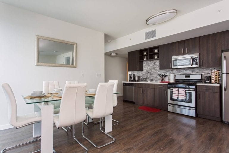 Open floor plan living space with a stocked kitchen and unique dining table