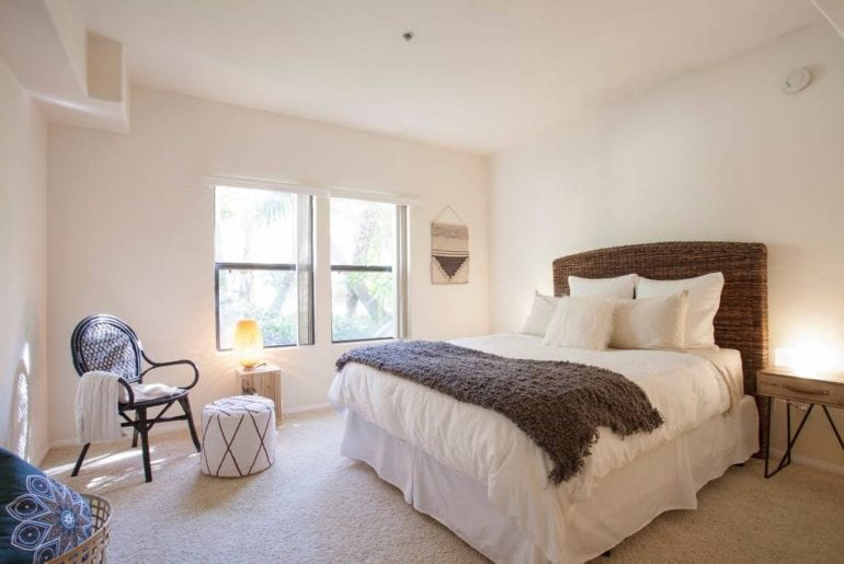 This bright and spacious bedroom has an inviting atmosphere and cozy features.