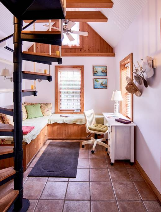 Folly Beach tiny home features a desk, wrap-around bench, and a spiral staircase