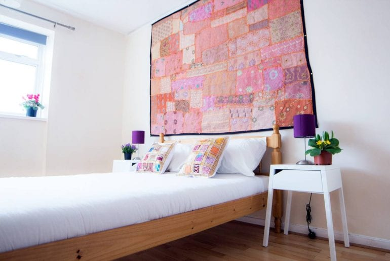 a pink patchwork quilt above a bed in an Airbnb in Westminster