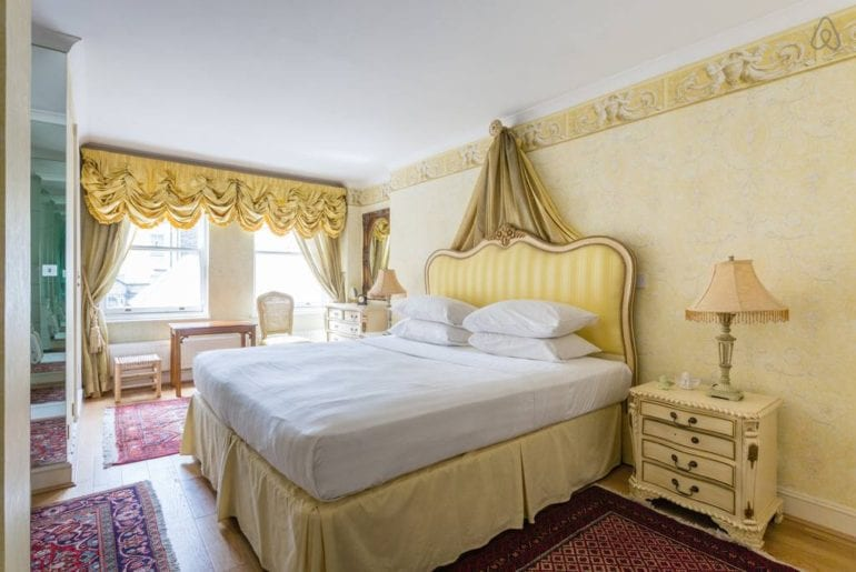 a bed with a gold headboard with some gold curtains behind it