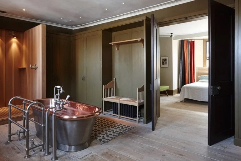 copper bath on wooden floors and green walls