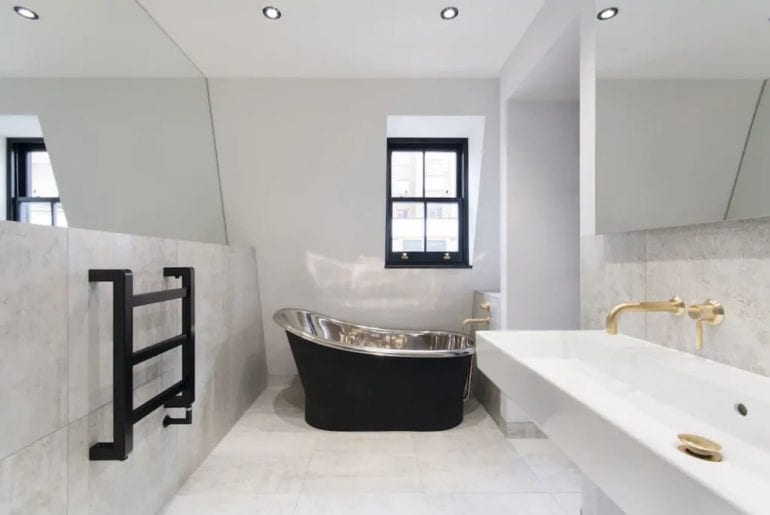 a stand alone silver bathtub in an angular bathroom