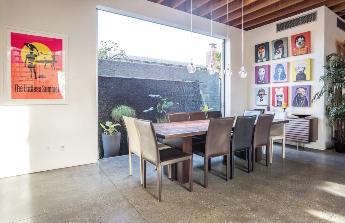 a concrete floored dining area with an endless summer poster in Los Angeles
