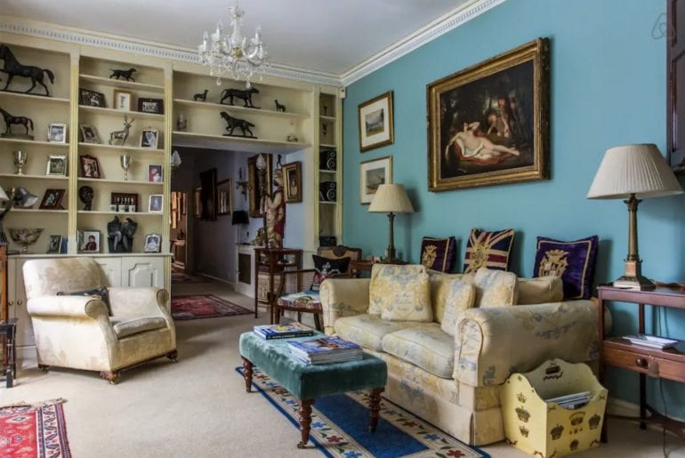 a Kensington living room with a painting of a nude woman above the sofa
