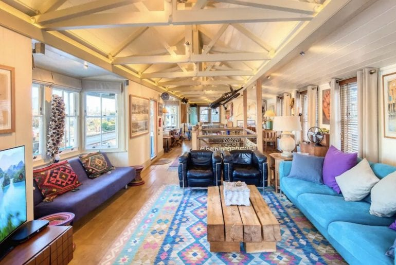 interior of houseboat on the Thames, blue sofas and wooden beams painted white
