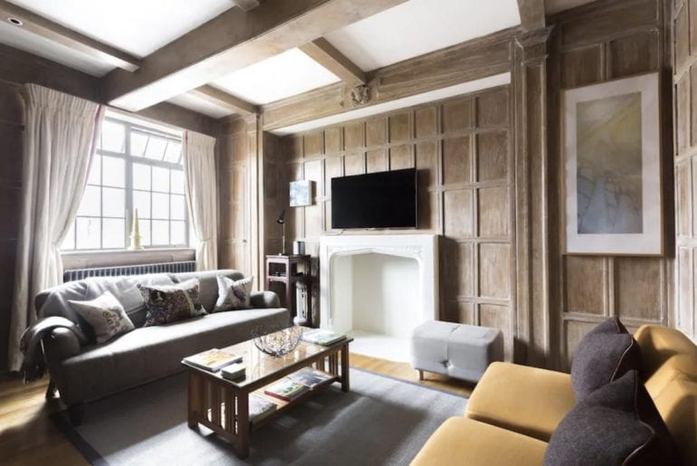 two sofas and a coffee table on a grey carpet in a wood panelled room