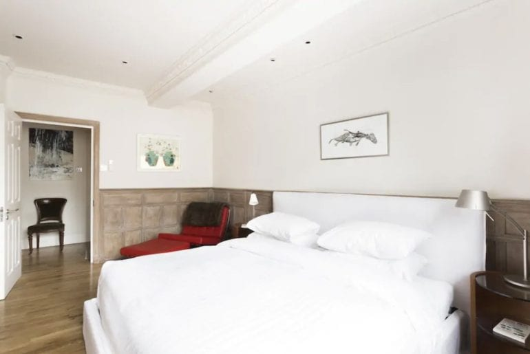 a double bed with white linen on it in a wood panelled bedroom