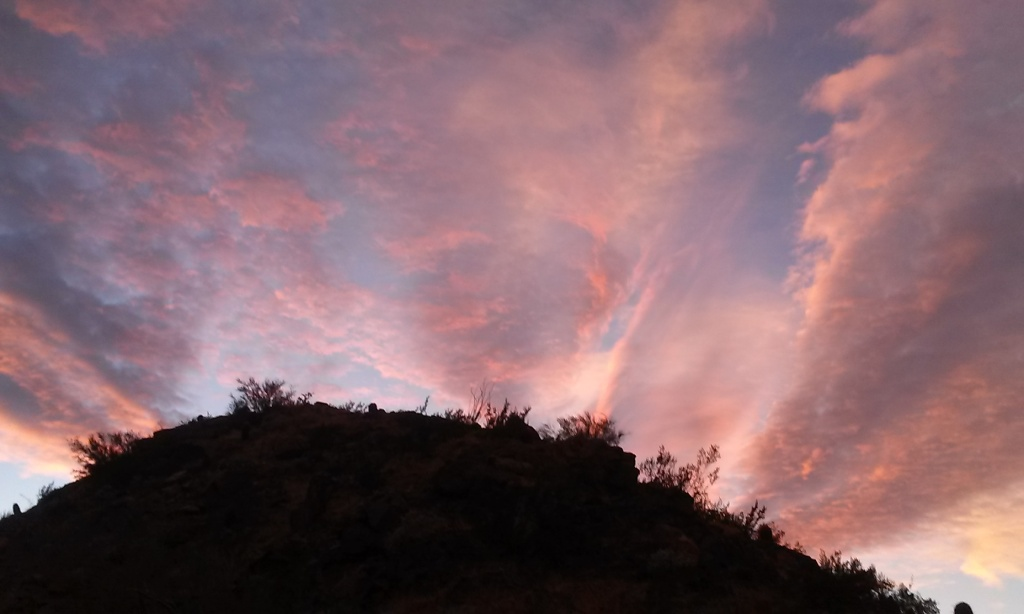 sunset clouds in pink and peach over dark hill