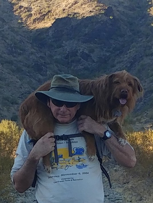 hiking dog being carried over shoulders