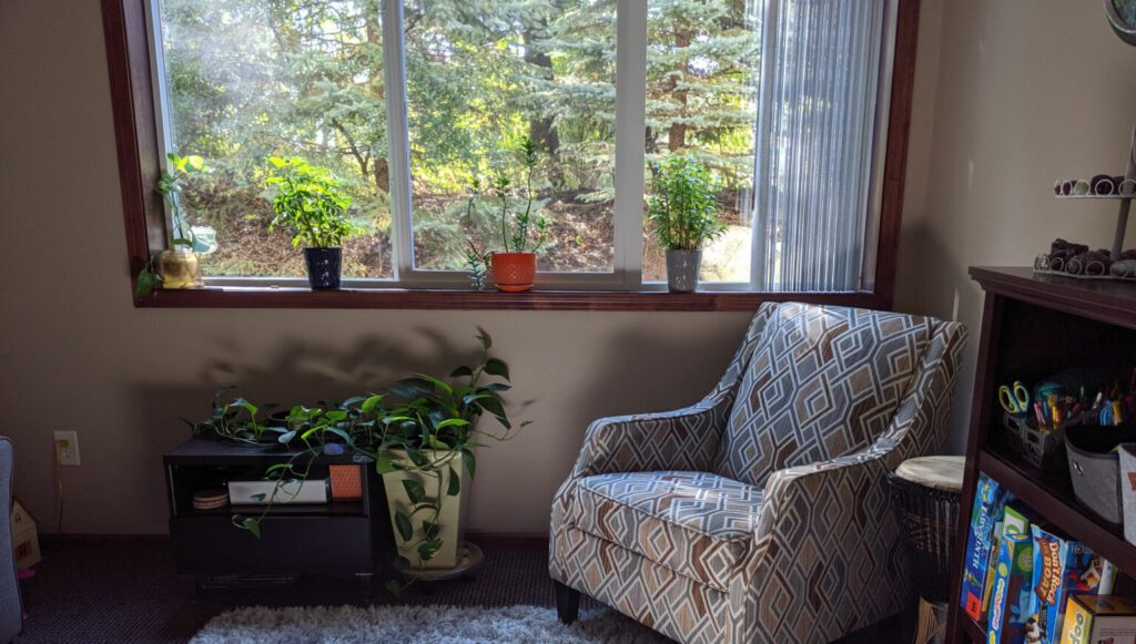 a lounge chair by the window with potted plants