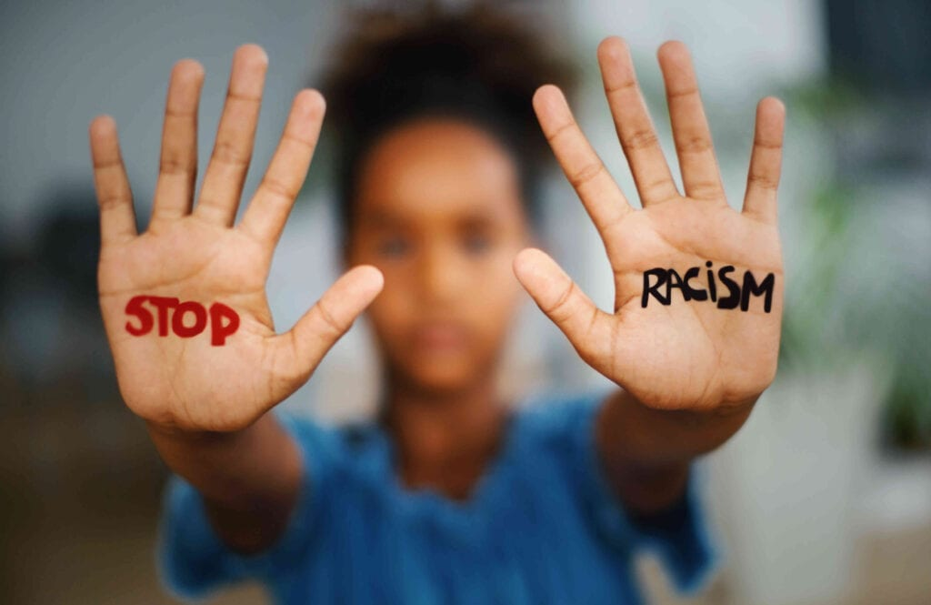 """A person holding up their hands with the words """"stop racism"""" written on each palm"""