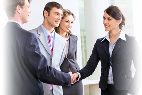 Four professionals standing shaking hands