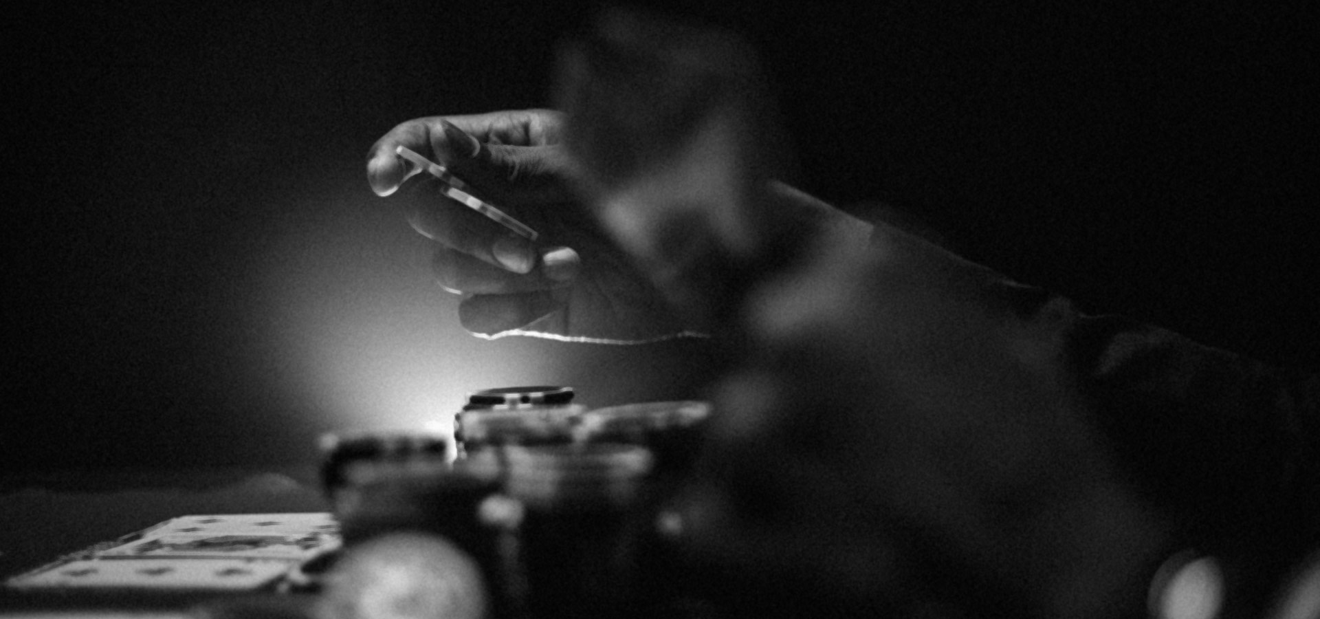 Black and white grainy photo of hand holding chips at card table