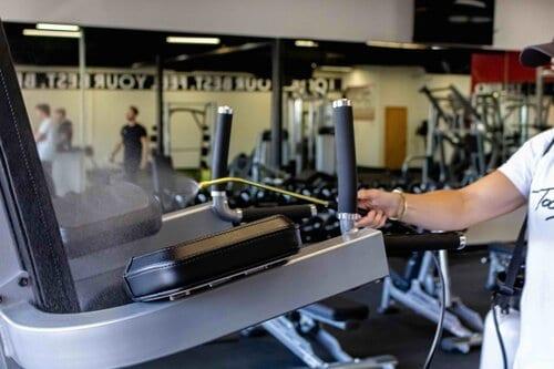 Gym staff sanitizing treadmill after use