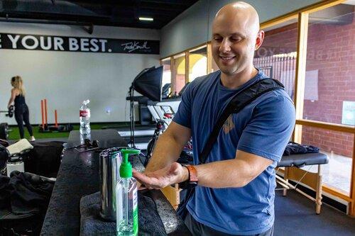 Gym Member Sanitizing with Hand Sanitizer