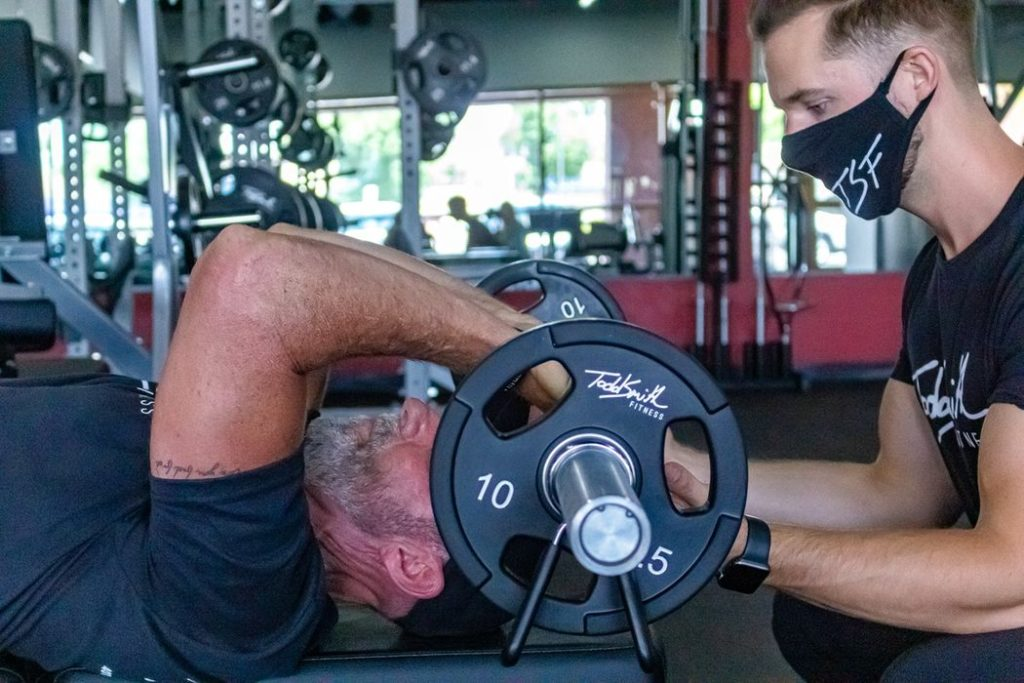 Personal trainer guiding a customer with weight training