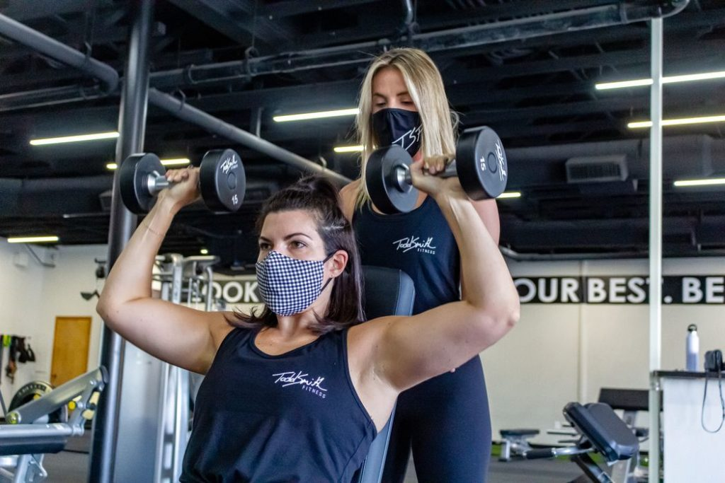 Fitness trainer guiding gym member in weight training exercise