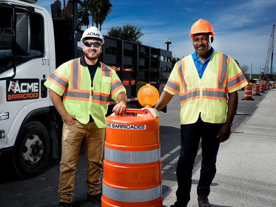Acme Barricades standing next to an orange barrel and traffic barricade rental