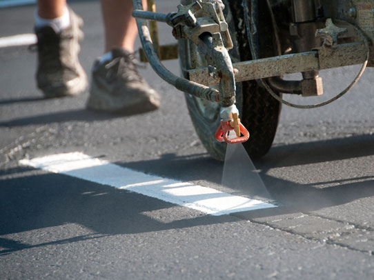 Acme Barricades Employee spraying traffic lines in florida
