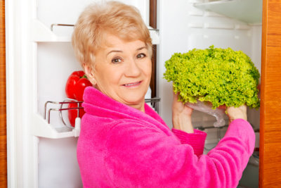 senior woman getting vegetable in the refrigerator