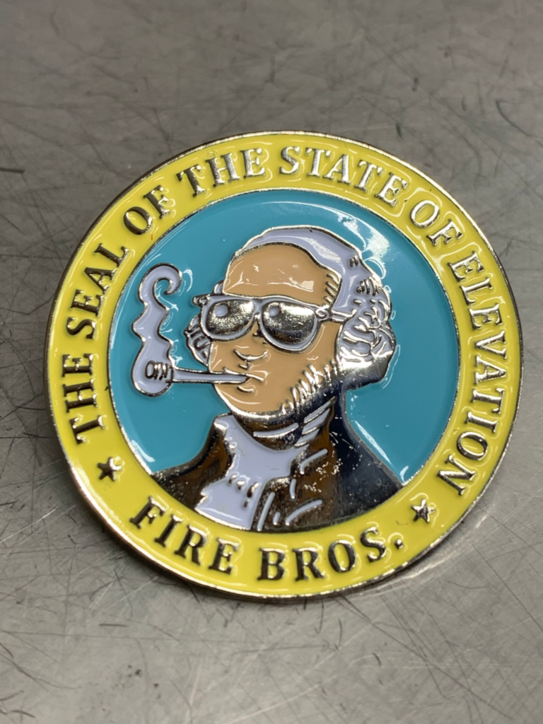 "Close up photo of enamel pin, inspired by the WA State Seal, it shows a cartoon General WA, with sunglasses on, with a smoking joint in his mouth.  Surrounded by text that says, ""The Seal Of The State Of Elevation, Fire Bros."